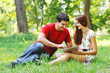 Couple relaxing together in summer park with tablet computer pc
