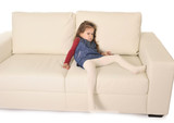 angry broed little girl with long hair lying on sofa