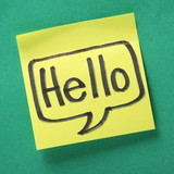 The word Hello in a speech bubble on a yellow sticky note