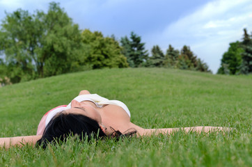 Young girl relaxing on the grass in a park
