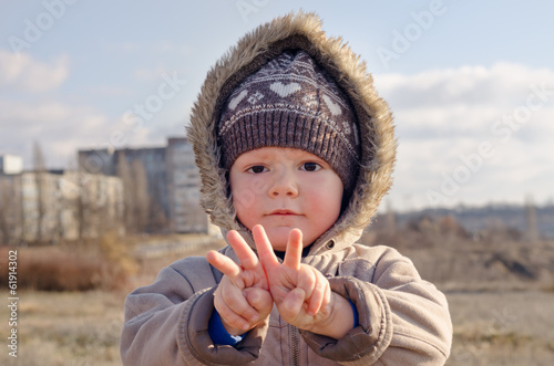 Cute young boy making V-sign gestures