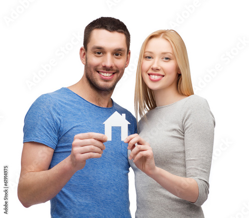 smiling couple holding white paper house