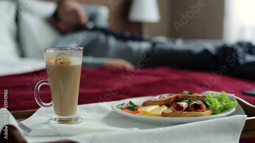 Wooden tray with tasty breakfast, businessman relax on hotel bed