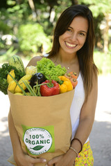 Happy woman carrying bag of organic food.