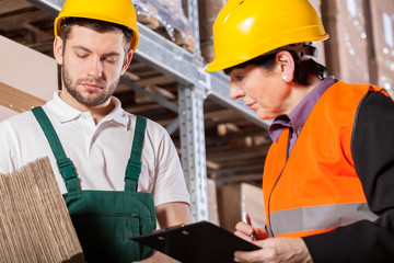 Worker consulting with manager in warehouse