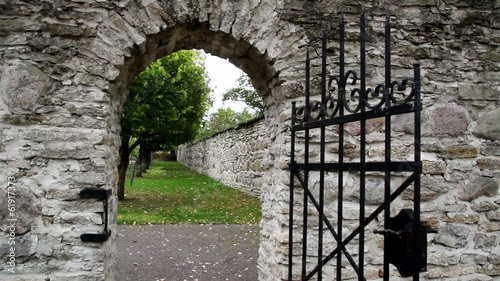 Stone entrance with an old medieval black steel gate