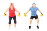 Mature man and woman working out with dumbbells