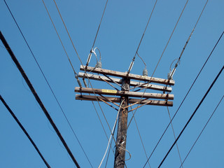 High Voltage Power Lines intersect at a wooden power pole