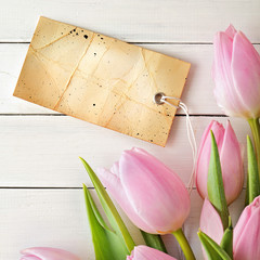 fresh tulips and blank note on wooden background