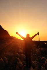 cheering hiking woman open arms at sunrise seaside