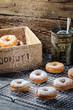 Closeup of falling icing sugar on fresh donuts