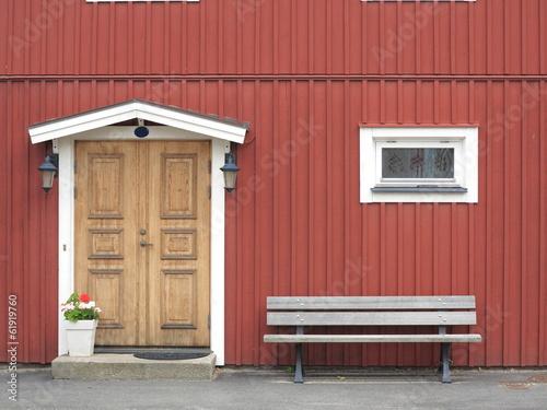 Wooden yellow door in red colored building - 61919760