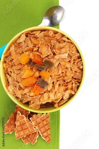 tasty cornflakes in bowl with dried fruits on green napkin