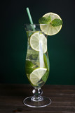 Glass of cocktail with lime and mint