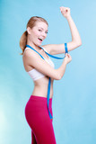Fitness girl sporty woman measuring her biseps on blue