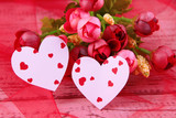 Paper hearts with flowers on table close up