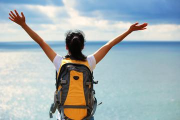 cheering woman hiker open arms seaside