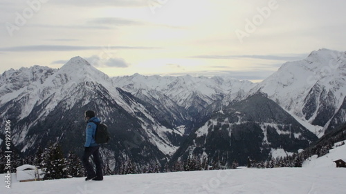 Woman with backpack walking in winter mountains, Alps