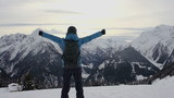 Woman standing on mountain peak with arms outstretched, Alps