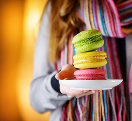 Young woman holding the french pastry macaron in cafe