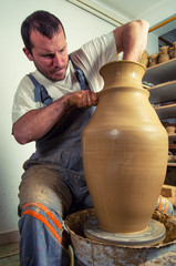 Craftsman making huge vase on pottery wheel