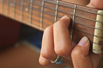 girl hand playing acoustic guitar