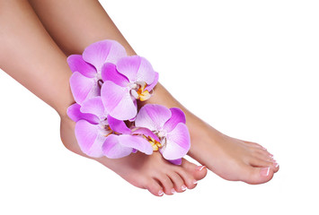 Pedicure with pink orchid flowers isolated