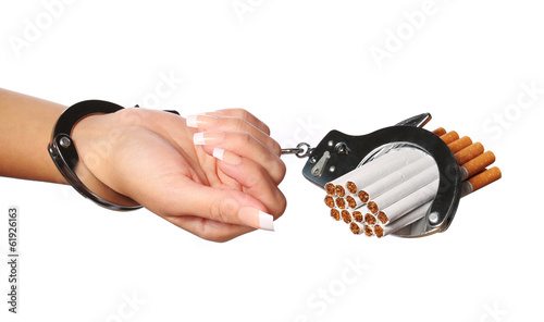 Cigarettes and handcuffs on female hand isolated on white