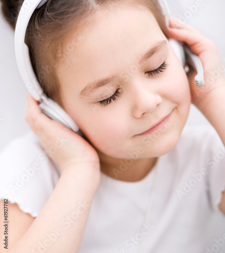 Little girl is enjoying music using headphones