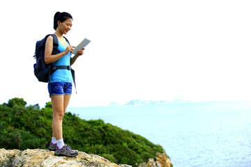 woman hiker seaside use digital tablet