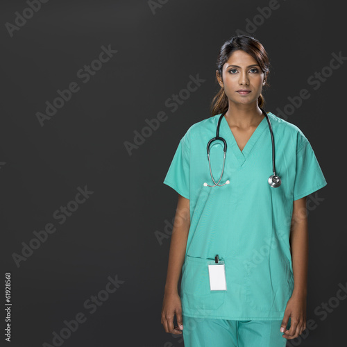 Female Indian doctor an dark grey background.