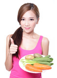 woman holding green vegetables and carrots