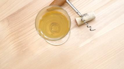 Corkscrew, cork and glass of white wine