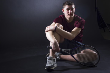 Male tennis player with tennis racket sitting