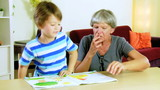 Dolly shot of grandmother helping kid with homework