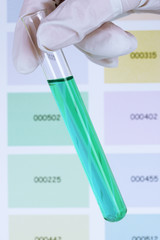 Tube with blue liquid in hand on color samples background