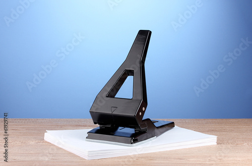 Black office hole punch with paper on blue background