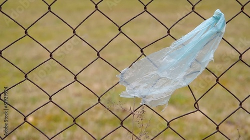 Plastic bag tied to a fence  flitting in the wind.