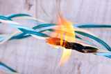 Short circuit, burnt cable, on color wooden background