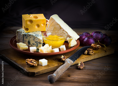 canvas print picture .Different varieties of cheese with walnuts and grapes