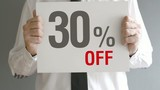 Salesman holding sale tag with thirty percent sales discount