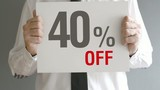 Salesman holding sale tag with forty percent sales discount
