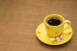 Yellow cup of coffee and a colorful candies on wooden rug