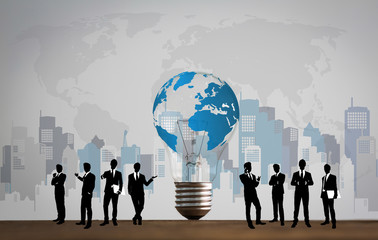 Business people silhouettes with bulb and world map
