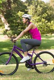 Fit young woman with helmet riding bicycle at park