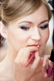 Closeup portrait of stylist painting brides lips with lipstick