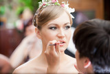 Closeup portrait of stylist making makeup for blonde bride