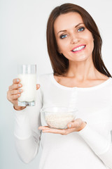 woman holding glass of mik and bowl with oatmeal