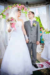 Beautiful bride and groom standing in alcove and holding hands