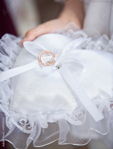 Closeup shot of witness holding white cushion with wedding rings